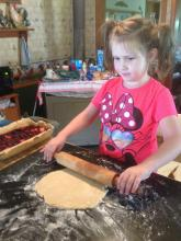 Photo of a blind girl rolling out pie crust.