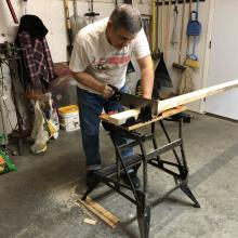 Photo of a blind man sawing a piece of wood.